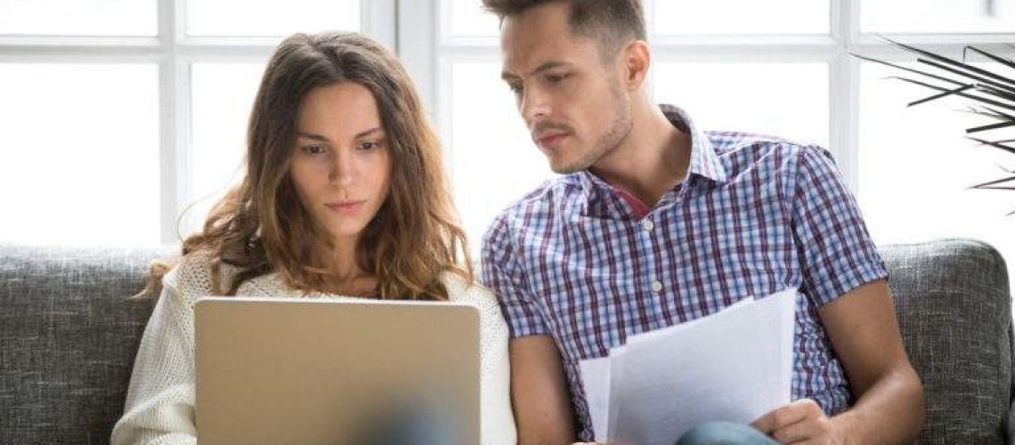 Focused worried couple paying bills online on laptop with documents sitting together on sofa at home, serious confused man and woman planning budget expenses, young family having debt loan problems
