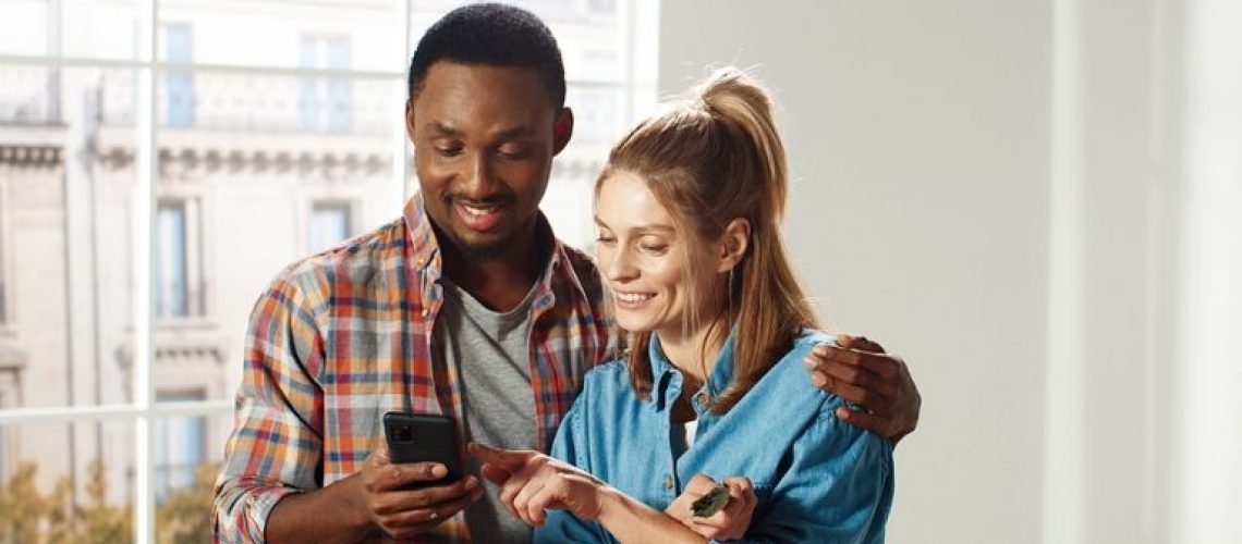 Joyful multi-ethnic young married couple Caucasian wife and African American husband hugging standing in room typing on mobile phone choosing design of new home. House repair. Renovation concept